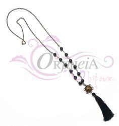 Collar con dije de metal, perlas esmaltadas y borla de color negro.