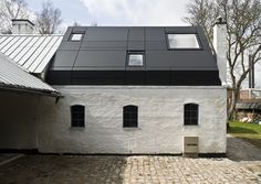 In Denmark, Svendborg Architects have adapted an old stable into an artist's studio by inserting a prismatic volume with an exaggerated pitched roof that directs light into the interior. The contrast between the black finish of the anodized aluminium addition and the white rendered walls of the stable evokes the aesthetic of the surrounding buildings with their traditional thatched and tiled roofs.