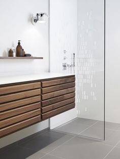 Bathroom with an elegant glass shower screen. Shower with linear floor drain. Elegant grating and frame in brushed stainless steel. Unidrain® GlassLine & ClassicLine