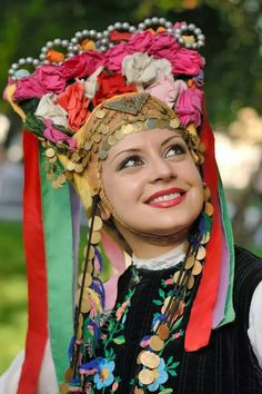 Woman wearing a traditional headdress ornamented with flowers and coins, Bulgaria