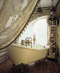 Gorgeous gauzy curtain covering a claw-foot tub... Dream bathroom right there.