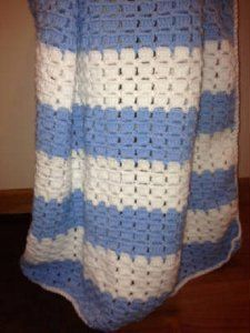 "Crochet this Baby Blue Afghan for any little boy or girl. Use shades of pinks and purples for a little girl or use a fun variegated yarn for either gender. This is great for beginners!  10 oz Main Color, 10 oz 2nd color,   WW yarn, J hook, Size: 32"" x 34"""