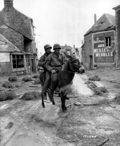 Two Americans using unusually low tech transport, France, July 8th 1944. Privates William Jackson and Joseph King of the 1st Infantry Division take advantage of Donkey transport on the Caen to Caumont-Evente road on July the 8th 1944. Behind them is the furniture company of Gestapo collaborator Julien Lenoir. The village of Caumont-Evente was liberated on June the 13th at 09:00 by Company F, 26th Infantry Regiment, 1st ID with support from the 742rd Tank Battalion.