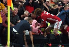 Marouane Fellaini helps a female Manchester United fan during his team's…