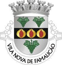 """Civic heraldry of Portugal - Brasões dos municípios Portugueses - Armas de prata com uma faixa de negro com três romãs de ouro abertas de vermelho. Em chefe, dois cachos de uvas de verde realçados de prata, folhados e troncados a verde. Em contrachefe, um cacho de uvas dos mesmos esmaltes. Coroa mural de cinco torres. Listel branco com os dizeres: """"Vila Nova de Famalicão"""", a negro."""