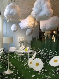 CONRAN SHOP | Such a cute idea to bring outside indoors with faux grass, clouds & oversized flowers. This display is especially impactful because of it's limited color palette. #visualmerchandising #windowdisplays