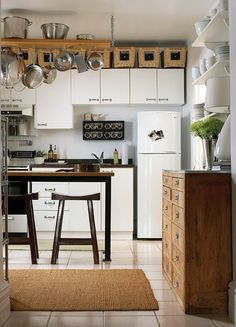 Small kitchen storage idea: put baskets above the cabinets to store lesser used items. Tall narrow bar table is the 'island'. BIG chemistry lab chest adds extra storage against the wall.