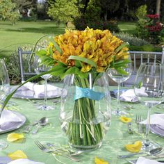 Pretty wedding centerpiece with yellow Peruvian lilies and blue ribbons