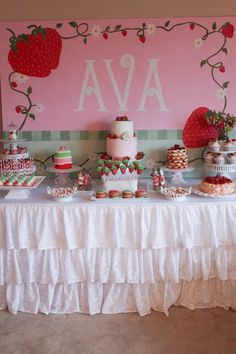 Strawberry Fields Birthday Party dessert table.  From the personalized backdrop to the strawberry cake pops to the ruffled table cloth, this summer party is super sweet.   #strawberryshortcake