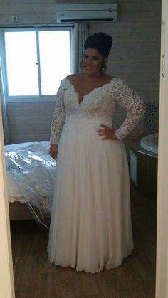 Stunning plus size bride in a corset dress with long sleeves V neck and a chiffone skirt