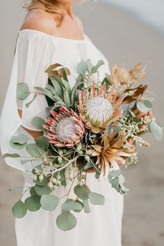 Gorgeous protea bridal bouquet // Eva Laszlo and photographer Peter Herman have teamed up to take us to a tropical paradise of unparalleled beauty. Shot in Villa Ethnic, Blue Karma Resort in Bali, Indonesia, the styled shoot features breezy dresses by Magali Pascal and Lulu Yasmine, flowers by Flower Corner Bali, desserts by Poule de Luxe, and hair and makeup by Sheryla Makeup & Bridal Studio.