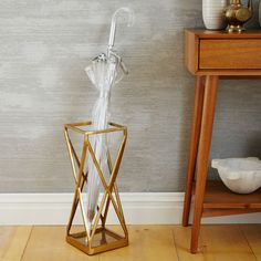 Stash soggy umbrellas with a side of sculpture - the geometric design of this antique brass-finished stand double as art.