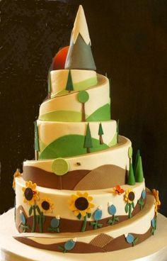 Hiking Theme Cake - This cake was for a couple who loves hiking.  The bride was from Texas so the bottom tier has Texas bluebonnets and sunflowers, the groom was from Oregon so as the cake graduates up to the top it gradually becomes more alpine, with pine trees, until finally reaching Mt. Hood at the top of the cake.  The bride wanted everything to be very graphic in style and brought me an inspiration picture from one of my favorite bakeries, Bakery Bar.