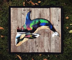 """This piece is made from using a perfect mix of reclaimed pallet wood and acrylic paint. An Orca whale cutout with the perfect amount of the colorful and bright northern lights to give it an accent. Measures at 18""""x16"""" and ships within 2 business days."""
