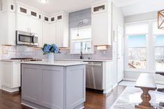 White stacked Shaker cabinets with a gray center island completes this classic look!  We sell high quality wood cabinetry, tile, hardware and customer counter tops.  Call Leslie Allison  913.706.2347