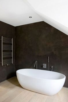 Dark Grey Venetian Plaster, Contrasts the stark white bathtub and ceiling giving this ultra modern bathroom the perfect finished look.  We offer Venetian Plaster Services of all types in the DFW Metroplex. Visit us online today! www.stuccofortworth.com