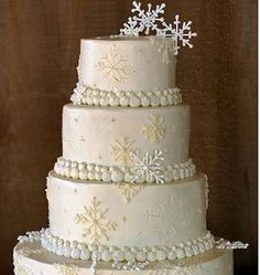 Hues of Ivory, Silver, Gold and White Combine On This White Fondant Wedding Cake With Snowflake And Pearl Embellishments To Make An Elegant Display.  Perfect for the winter wedding.