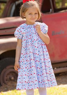 There's something about florals! Our Lilly Kate Smocked Dress is made from beautiful red, white, and blue floral fabric, hand smocked and hand embroidered flower detailing.  Buttons down the front. See size chart. 100% cotton.