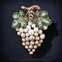 Antique Plique-a-Jour Enamel and Natural Pearl Grape Cluster Brooch.This enchanting grape cluster brooch shimmers with a 'bunch' of natural pearls of various colors and hues. These luscious fruits (of the sea) are crowned with translucent, shaded green plique-a-jour grape leaves accented with teeny-tiny twinkling diamonds.
