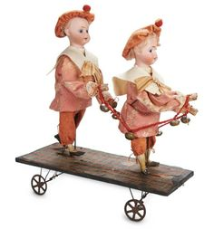 """French Mechanical Pull-Toy """"Merry Twins with Garland of Bells""""--When pulled along, the dolls wave their arms up and down, ringing the garland of bells they hold. Condition: mechnaism functions well, one doll has crack and reglue on one side of face. Marks: 179 2/0 (dolls). Comments: for the French market, circa 1890. Value Points: the charming mechanical toy is all original, the twin brothers wearing their factory-original costumes."""