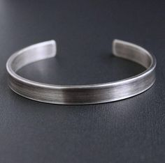 Thick gauge sterling silver flat metal has been forged into this mens unembellished metal cuff bracelet. The silver band has been oxidized and given a sanded, matte finish. A sleek, simple, and modern look! Silver band measures 8 mm wide. Cuff can be made in the following sizes