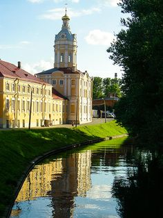 Reflection in water of canal of historic buildings at Alexander Nevsky Monastery in St Petersburg Russia