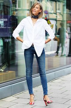 A white button-down shirt is paired with skinny jeans, heels, and a neckerchief