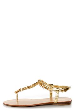 """Bamboo: Sterno 70 Gold Rhinestone T-Strap Thong Sandals- Indulge your love for luxury in these sparkling sandals! Gold metallic faux leather sandals have a thong-style T-strap thats covered in glittering gold and white rhinestones from toe to quarter, with an adjustable strap that fastens with a gold buckle (and hidden elastic). Protective plastic covering on toe thong. 1/2"""" wooden-look silver wedge heel. Genuine leather insole with tonal top-stitching. Non-skid rubber sole. Leather insole…"""