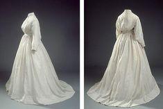 Lange jurk in witte stof met kleine, rode ster patroon.  De jurk heeft lange mouwen en een kleine sleep.