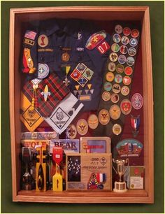 custom wood shadow box for an eagle scout. This box displays a scout's career history and includes handbooks, pinewood derby cars, and tiger cub achievement beads (other shadow box ideas on this page, too) Tiger Scouts, Cub Scouts, Girl Scouts, Conquistador, Eagle Scout Gifts, Eagle Scout Ceremony, Arrow Of Lights, Award Display, Wood Shadow Box