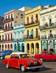 Standards of the Havana streetscape—arcaded pastel buildings and brightly colored pre-1960 American automobiles.