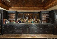 A fantastic dark wood home bar with stone tile flooring and distressed cabinetry.