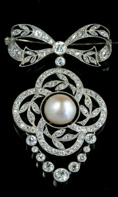 "BELLE EPOQUE BROOCH/ PENDANT. Western Europe, 19th Century, A bow-shaped platinum brooch / pendant put with old cut diamonds and in the middle a large natural pearl. ""Belle Epoque"", 1900, Dimensions:. 5 x 3.5 cm"