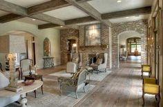 Beamed ceiling, wide plank wood floor, brick wall, arched doorways.