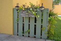 An adorable mini garden fence made from a pallet. Notice the little flower box and solar lights.
