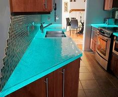 Recycled glass countertops glowing green: These have a tapelight at the counter's back edge that turns the glass from transparent to glowing at night. Pretty, and useful for late night snacks! #smartcommunity