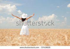 Happy woman in golden wheat by suravid, via Shutterstock