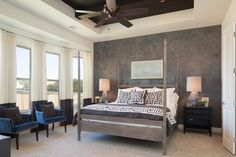 Venetian plaster creates a striking backdrop in our Luxury Garden Home's master bedroom. We decided to add subtle accents of Navy to compliment the grey and kept the patterns bold to make the bed the focus point upon entering.