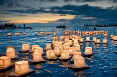HONOLULU.  These floating lanterns memorialize those that have passed away at Ala Moana Park in Honolulu, Hawaii.  As the sun sets in the background, small boats with Buddhist monks and church volunteers help to launch and shepherd the small armada of lantern ships, each inscribed with sentiments from family and friends.