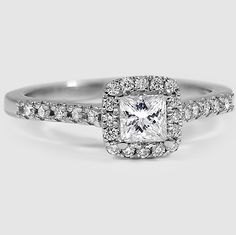 French pavé diamonds surround the center gem and sparkle along the band in this dazzling halo engagement ring.