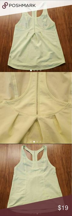 Lululemon Lightened Up yellow tank Good/fair condition yellow racerback tank/singlet. Color is more neon, brighter than pics. Small flaws like a faint spot in front you can see if inspected closely and some faint dirt lines on back by pleating in 2nd pic. Hard to show and see. Material and color are very good. Just washed. No rip tag or size dot. I wear 6 and this fits with a little room on the side for a loose fit.  Use measurements to ensure fit. Approx 15 inches armpit to armpit, 25 in…