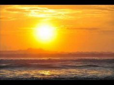 A vibrant orange sunrise brightens the sky as ocean spray mists off the waves at the beach in Florida.