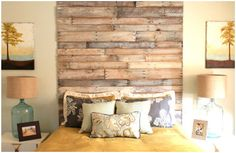 Wooden headboard made of pallet wood. White washed and nailed right to the wall it goes up to the ceiling. :)