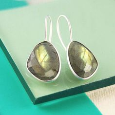 These elegant irregular drop earrings feature a beautiful faceted semi-precious stone suspended from brushed 18 carat gold hooks. #Embersjewellery #Jewellery #Giftforher #Labradorite