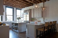 Under wood ceiling beams, this stunning loft kitchen features two Arteriors Beck Pendants hung over a light gray peninsula painted in Farrow & Ball Dove Tale and topped with a white marble countertop.