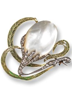 An Art Nouveau floral brooch, mounted with a large blister pearl, set with rose-cut diamonds in silver and gold mounted plique-à-jour enamel scrolls. #ArtNouveau #brooch