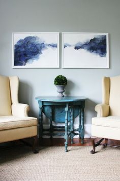 A small space dining room with wingback chairs, drop leaf table, and watercolor diptych
