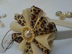 Tiara de cabelo bebê e infantil feito de tecido cetim estampa oncinha e marfim, com detalhe em pérola, strass ou chaton.. R$ 16,90