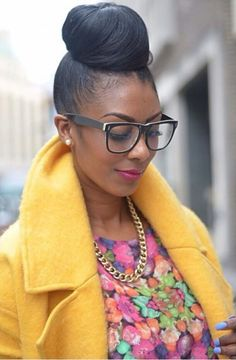 Neat top bun, oversized glasses, pink neon lippy, mustard coat with oversized lapels and multicolour floral top
