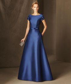 O modelo que a transformará em princesa. BRIA é um vestido de madrinha realizado em mikado, decote em barco e detalhes de pedraria na manga curta e nas costas.